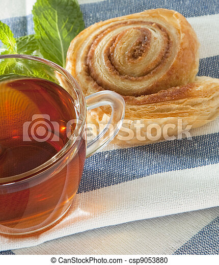 Cup of tea with cinnamon Danish bun - csp9053880