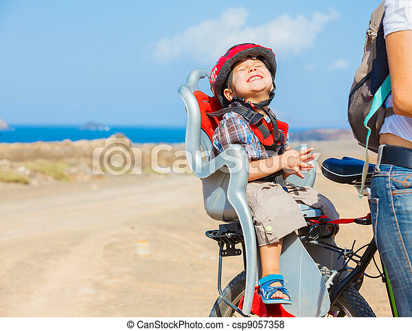 child sitting by bicycle in crash helmet - csp9057358