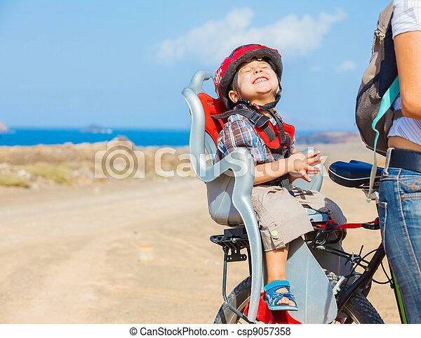 child sitting by bicycle in crash helmet - csp9057358