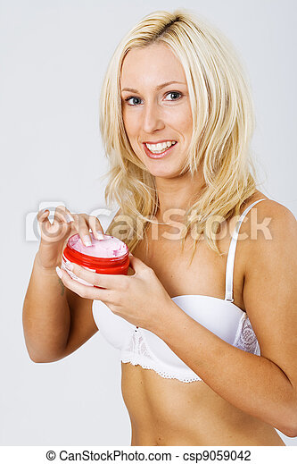 Gorgeous blond applying lotion and makeup - csp9059042