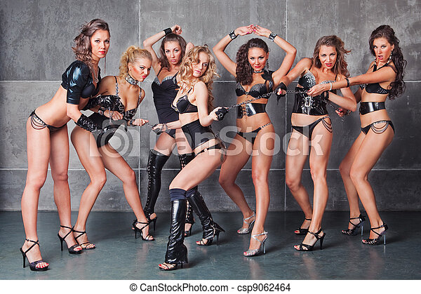 Seven Cute go-go sexy girls in black with diamonds costume pulling a chain - csp9062464