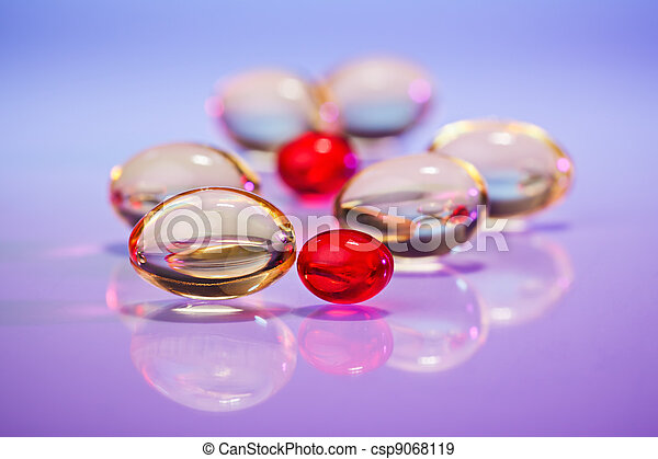 Pills (capsules) of cod-liver oil on violet, macro view with selective focus - csp9068119