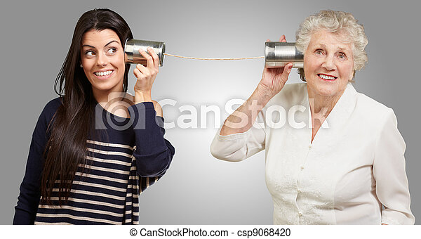 portrait of young girl and her grandmother hearing sounds using a metal tin can - csp9068420
