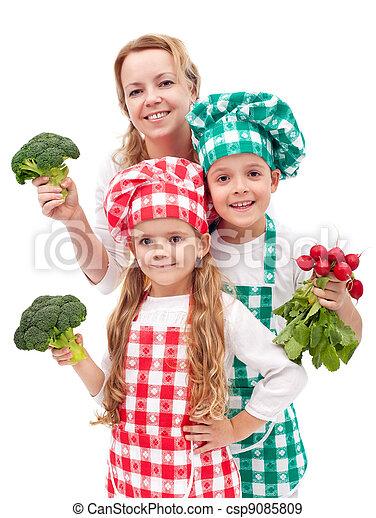 Happy family preparing healthy vegetables meal - csp9085809