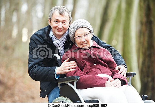 old senior woman in wheelchair with careful son - csp9091992