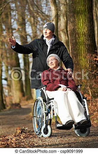 elderly woman in wheelchair walking with son - csp9091999