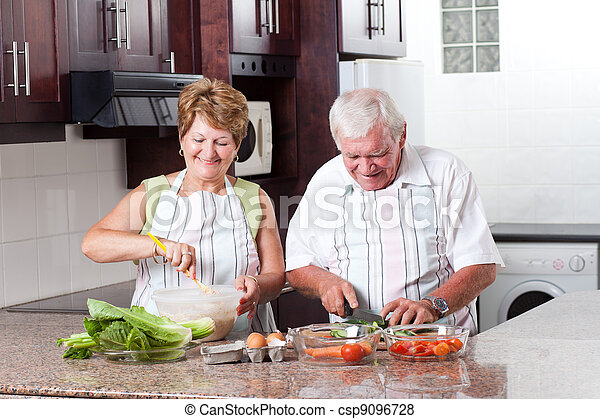 elderly couple cooking in home kitchen - csp9096728
