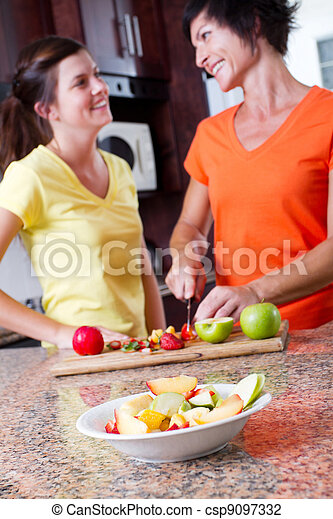 middle aged mother and teen daughter cooking - csp9097332