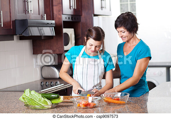 mother teaching teenage daughter cooking - csp9097573