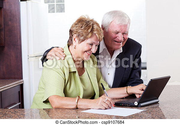 happy senior couple using internet banking - csp9107684