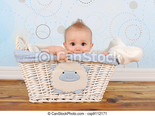 handsome baby boy peeking out of wicker basket - csp9112171