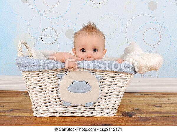 handsome baby boy peeking out of wicker basket - csp9112171
