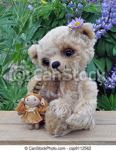Teddy-bear Lucky with a rag doll on the board against a background of flowers. Handmade, the sewed toy