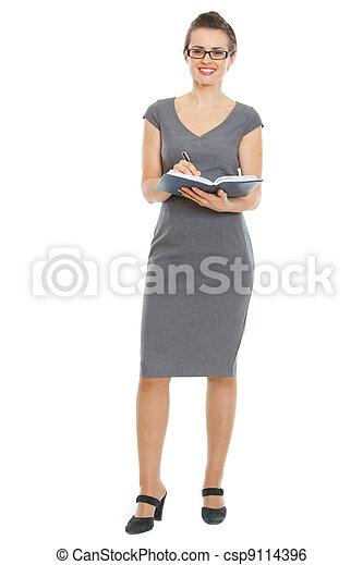 Female teacher writing in notepad - csp9114396