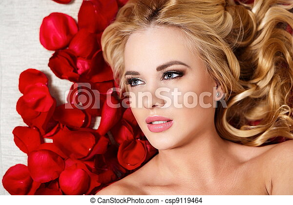 closeup portrait of beautiful blond dreaming girl with red roses long curly hair and bright makeup - csp9119464