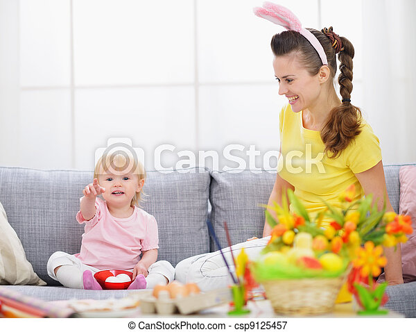 Mother and baby making preparations for Easter - csp9125457