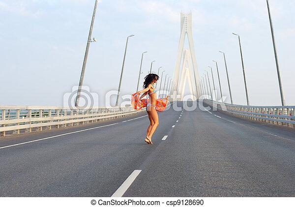 Young adult walking over  bridge - csp9128690