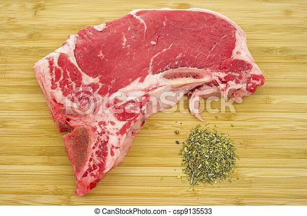 T-bone steak on cutting board with seasoning - csp9135533