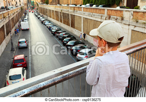 small boy standing on bridge, holding hands on railing and looks down road - csp9136275