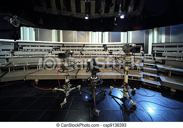 three professional black video cameras in television studio, seats for audience - csp9136393