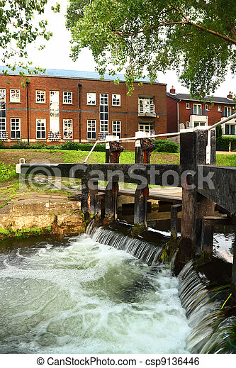 artificial waterfall and river. small houses made of red brick - csp9136446