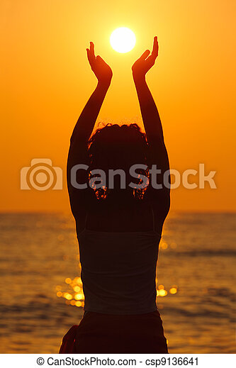 beautiful young woman standing on beach, watching sunset, holding  sun in hands - csp9136641