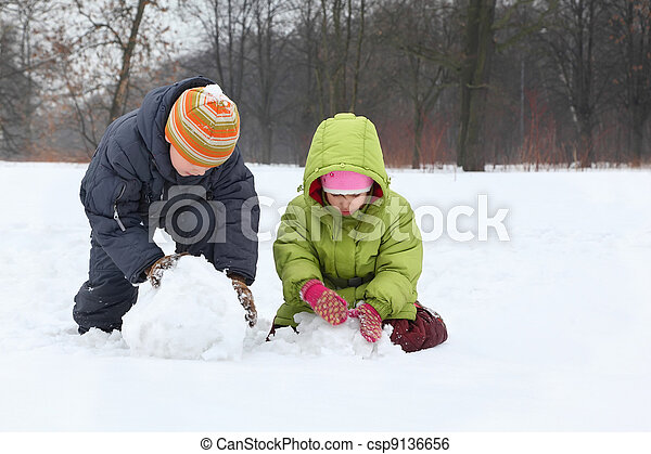 Brother and sister sculpt snowman in street in winter - csp9136656