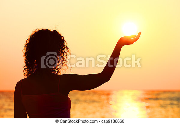 beautiful young woman standing on beach, watching sunset, holding  sun in hand - csp9136660