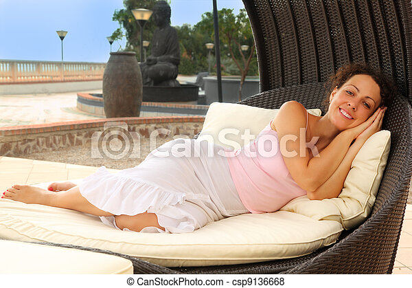 beautiful young woman lying on white cushions in black wicker chair, statue, trees and lanterns - csp9136668
