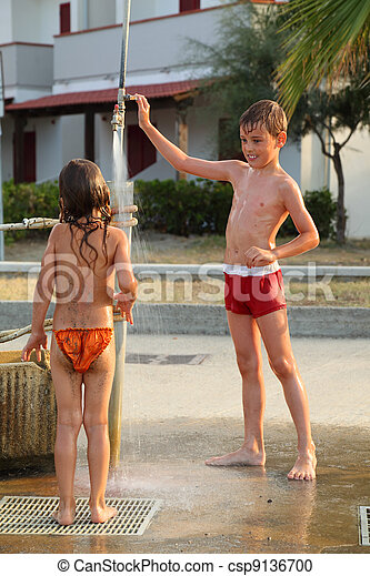 little brother and sister are taking outdoor shower after swim, focus on boy - csp9136700