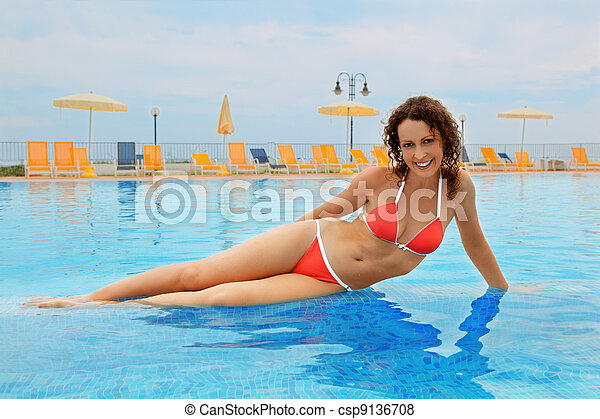 beautiful young woman in red bathing suit sitting in pool. yellow chairs and beach umbrellas - csp9136708