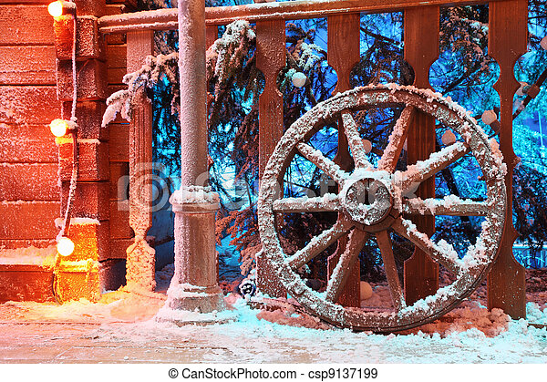 Wooden wheel in snow stand near beautiful railing; Spruce in snow behind railing - csp9137199