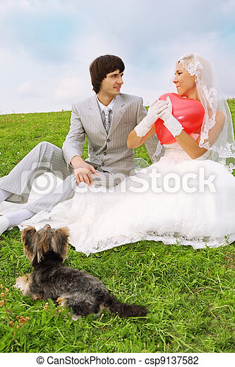 Beautiful young groom and bride wearing white dress sitting on green grass; bride keeps heart-shaped red balloon; small dog lies near couple - csp9137582