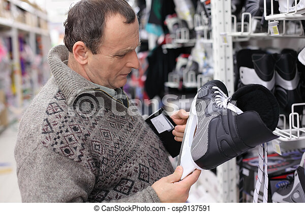 elderly man in gray sweater chooses skates in big sports shop - csp9137591