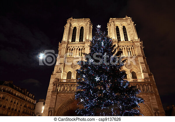 Christmas tree in front of Notre Dame and the moon shines through the clouds - csp9137626