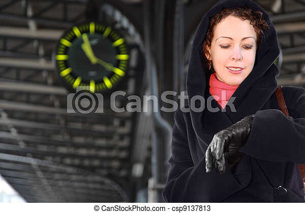 Young woman looks at her wristwatch, standing on the railway platform. - csp9137813