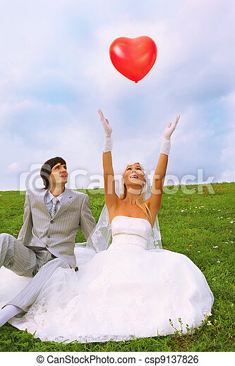 Beautiful young groom and bride wearing white dress sitting on green grass; bride throws in sky heart-shaped red balloon - csp9137826