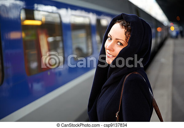 Young smiling woman close-up stands on the platform near the train. - csp9137834