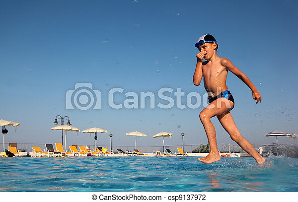 little boy with glasses for swimming dives into blue, clear water of pool. in background beach umbrellas. from the underwater package - csp9137972