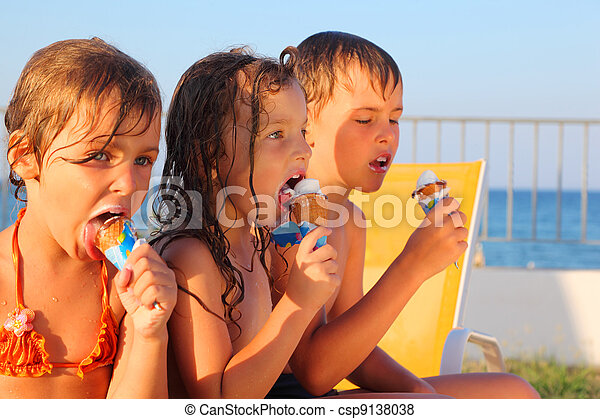 little brother and two sisters in swimsuits on beach eating ice cream after bath. focus on girl in middle - csp9138038
