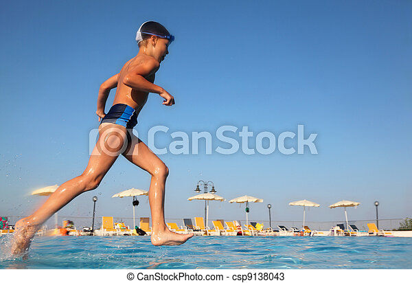 little boy with glasses for swimming runs and dives into blue, clear water of pool, beach umbrellas, from the underwater package - csp9138043