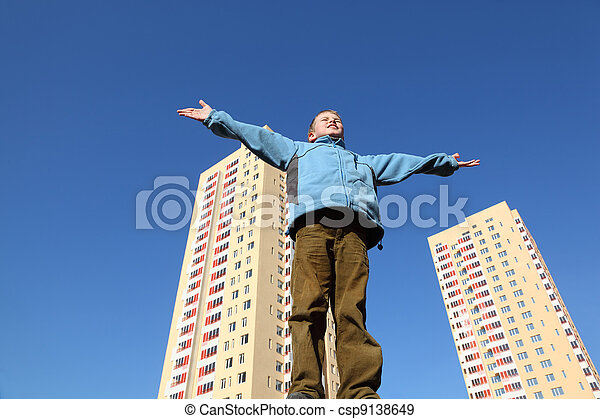 little boy in blue jacket raises his arms to blue sky. In background two multi-story yellow houses - csp9138649