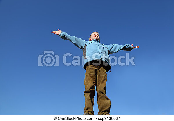 little boy in blue jacket and brown pants raises his arms to blue sky - csp9138687