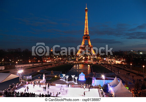 PARIS - JANUARY 2: People skate at night on January 2, 2010 in Paris, France. Eiffel Tower is highest monument in France (324 metres) use 20000 light bulbs in show. - csp9138887