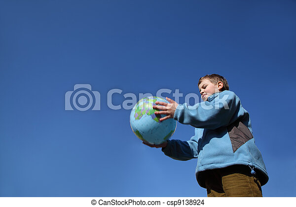 little boy in blue jacket and brown pants holding balloon in form of globe - csp9138924