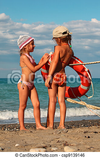 two little sisters in swimsuits standing on beach near metal pole, on pole hanging red life buoy - csp9139146