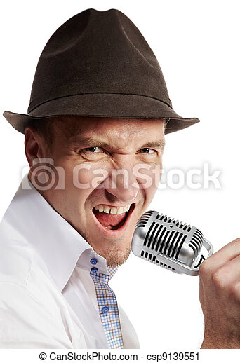 Man in the brown felt  hat sings expressively into the microphone. - csp9139551