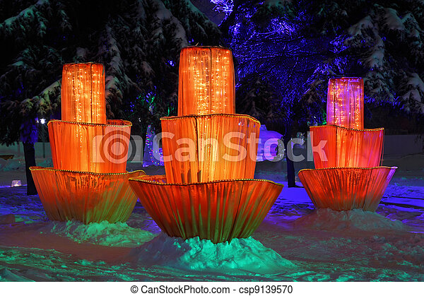 Three fairytale multilayer flowers and icy figurines among trees during an icy rain on Christmas - csp9139570