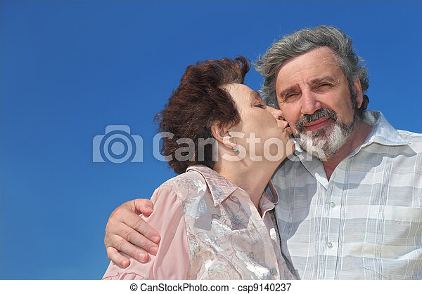 portrait of old woman kissing man cheek, blue sky - csp9140237