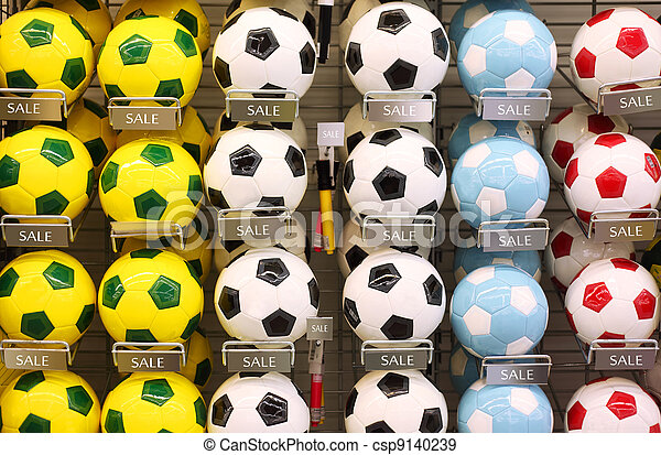 Rows of white, yellow and blue classic soccer balls in store - csp9140239